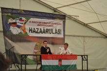 """Jobbik President Gábor Vona (left) and National Assembly representative Sándor Pörzse. The sign in the background reads """"Playing Hungarian Land off into the Hands of Foreigners: TREASON!"""