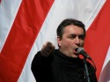 Reformed pastor Loránt Hegedűs Jr. speaks in front of an Árpád-Striped Flag during an anti-government rally on the March 15 national holiday (March 15, 2008).