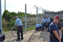 Prison workers extend the fence to the last gap in the border.