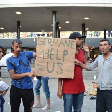 Refugees with sign.