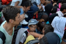 Refugees waiting to board bus at the regular border.