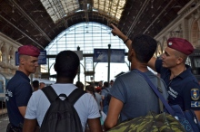 Cop helping refugees to decipher the train schedule.