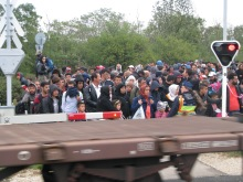 Migrants wait for train to pass outside Hegyeshalom.
