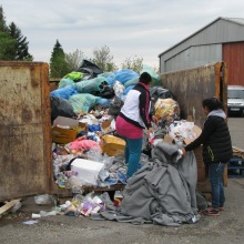 Gypsies remove discarded UNHCR blankets from dumpster near border.