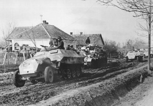 German armored vehicles advance down muddy road during Operation Spring Awakening.