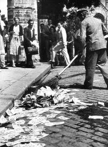 Sweeping worthless pengő banknotes from the street in Budapest.